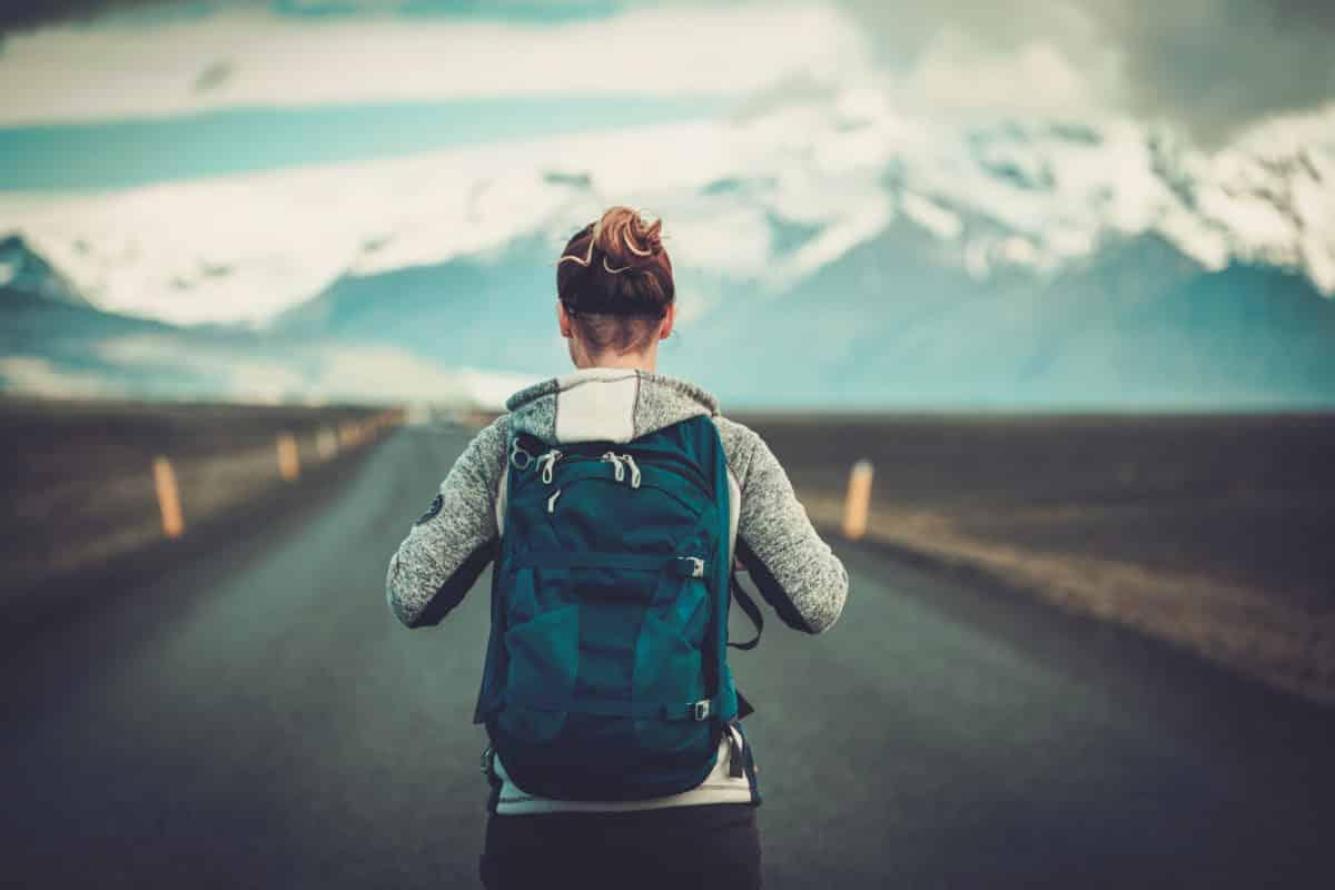 travel-hitchhiker-woman-walking-on-a-road-PC7CTJ7-1200x800.jpg